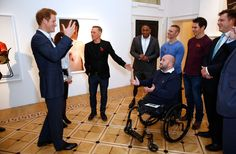 RH Prince Harry talks to photographer Bryan Adams and servicemen at the private view of 'Wounded: The Legacy of War' at Somerset House on Remembrance Day, November 11, 2014