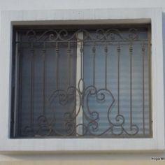 Rejas de hierro instaladas como protección de ventanas con un diseño de herrería artística.