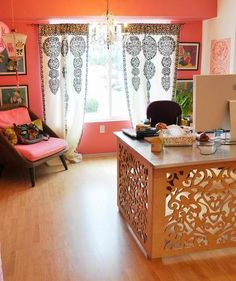 cool carved wood desk + peachy pink walls + cozy chair + pretty chandeliers + asian art print