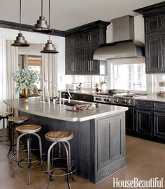 The color of the finish on the cabinets changes with the light, but the gray undertones blend in with the antique iron pendants from John Rosselli and the custom rolled-steel hood. Wolf cooktop with grill. The Kensington bar stools made by Arhaus are made from reclaimed pine and iron.   - HouseBeautiful.com