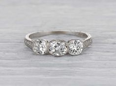 Antique late Edwardian engagement ring made in platinum and set with three EGL certified old mine cushion cut diamonds weighing approximately 1.43 carats total. The center stone has H-I color and SI1 clarity. Circa 1919.