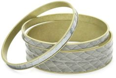 """Helene Jewelry 3 Grey Genuine Snake Skin Bangle Bracelet Set Helene Jewelry. $14.99. Two tones of exotic inspiration adds a subtle opulence. Multiple widths create substantial style. Width of each skinny bangle: .25"""", width of wide bangle: .75"""". Made in United States. Matte grey and metallic silver encircle each brass bangle. Save 80%!"""