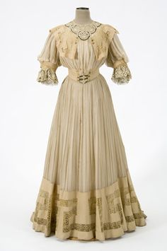(View 1 without tunic) 1905 Woman's suit constructed of light yellowish brown wool and yellowish white silk chiffon is trimmed with lace of embroidered net underlaid with cloth of black and gold threads. Suit day bodice consists of a tunic length jacket open from waist with an uneven hemline and train.