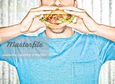 Close-up of Man eating Cheeseburger, Studio Shot  – Image © Dana Hursey / Masterfile.com: Creative Stock Photos, Vectors and Illustrations for Web, Mobile and Print