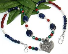 This unique handmade necklace brings together blue lapis lazuli gemstones, an ornate pewter bird pendant, green malachite rounds, faceted red coral,