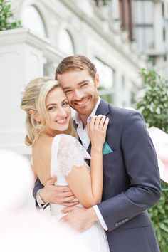bride and groom smiling and cuddling at the entrance of the mandarin oriental hotel in london