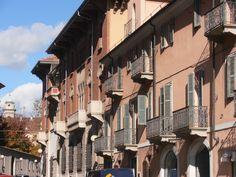Due caratteristiche dei palazzi storici di questo quartiere: i piccoli balconi a ringhiera con persiane in legno e le vetrate colorate per interni ed esterni