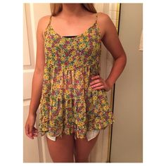 Floral top Tank top with an open back and yellow green pink and blue flowers. Can possibly be worn as a dress if you're shorter:) in perfect condition and not really Brandy just under it for views!:) Brandy Melville Tops