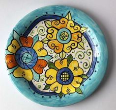 I love to paint pottery in floral, textile inspired, and graphic colorful patterns. Each piece I paint is completely different. The front and