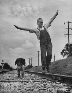 Iowa boy walks railroad tracks with his dog, 1945. From our gallery Kids and their Pets.