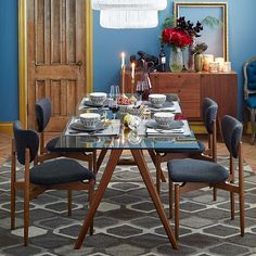 A solid wood A-frame base and clear glass top give the retro-inspired Jensen Dining Table a light look that pairs well with upholstered chairs.