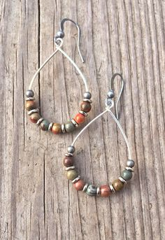 Silver hoop earrings with red creek jasper and oxidized silver accents. Light…