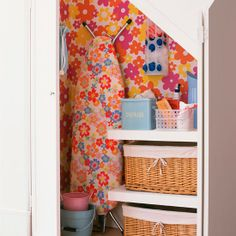 Don't have a utility room? Devote a cupboard to the cause. Include a storage unit with rattan baskets for cleaning products, use it to tuck away your ironing board and define the area with a pretty wallpaper.
