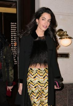 Amal Clooney was spotted stepping out in New York on March 24, 2015.  She wore chevron trousers  by Giambattista Valli Pre Fall 2015 collection with a geometric clutch, black coat and fur top.