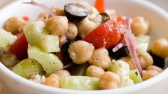 This is a delightful salad that doesn't skimp on taste.   Ingredients 2 (15 ounce) cans garbanzo beans, drained 2 cucumbers, halved lengthwise and sliced 12 cherry tomatoes, halved 1/2 red onion, chopped 2 cloves garlic, minced 1 (15 ounce) can black olives, drained and chopped   1 ounce crumbled feta cheese 1/2 cup Italian-style salad dressing 1/2 lemon, juiced 1/2 teaspoon garlic salt 1/2 teaspoon ground black pepper