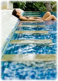 A swimming pool with built in sun chairs.  Perfect. The reflective rays from the water help create a luminous tan. Plus getting in water after sun bathing makes your tan last even longer. What a luxurious and fine thing to have outside your home.  MUST HAVE