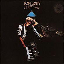 "A man leans against a piano in a dark room. The arched text above him reads ""Tom Waits Closing Time."""