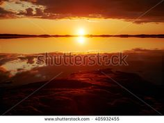 Stock Photo: Sunset with crimson red color in the clouds and the rocks on the shore. Dramatic reflection of the Sun in the still water of a lake in Finland.