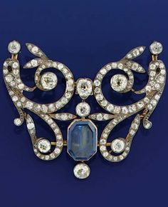 A Sapphire and Diamond brooch,  of openwork symmetrical scroll design with central rectangular cut- cornered Sapphire, set throughout with old circular and cushion cut Diamonds, mounted in silver and gold, circa 1900, later adaptations.