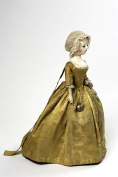 Doll, 1740-50. In the 18th century, dresses fastening at the back like this were for children, not women. Long streamers of matching fabric (leading strings) at the back of the dress indicate she represents a teenage girl. Leading strings helped adults assist a child learning to walk. In the 18th century they also became customary for unmarried teenage girls, perhaps to symbolise the fact that they were still under parental control.