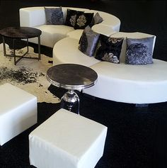 Luxor modular curved seating with Ellora side table, accent pillows, cowhide rug, and Luxor cube ottomans.