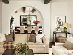 Spanish Revival Bungalow with dark-wood beamed ceiling features a Neutral Contemporary Living Area, dark wood floors, beautiful arched openings.
