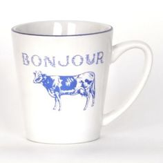 Part of our farmhouse dining collection, the white Bonjour beverage mug comes trimmed in blue with a decorative cow stamp under the lightly distressed script. #Kirklands #FrenchCountryDining #Bonjour #mug