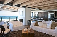 Matthew Perry's open plan living area has floor-to-ceiling glass panels with views of the pounding surf
