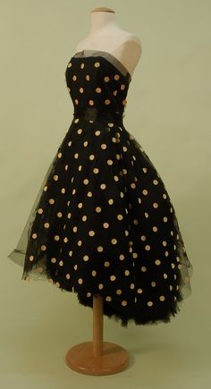 "LANVIN CASTILLO, PARIS, DOTTED TULLE STRAPLESS DRESS, c 1950. Black silk with boned bodice and full layered skirt dotted in bone velveteen, back cut to reveal a ruffled tulle bustle effect on underskirt with many layered tulle hem ruffle, silk satin waistband and braided back bow detail, side zipper, skirt back closes to hem with hooks & eyes. Labels ""Jeanne Lavin Paris"" and ""Castillo"". Front"