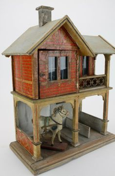 """Gottschalk stable with coachmans quarters: painted and lithographed paper on wood, features include 2 stalls with metal hay racks and 2nd story apartment with glazed window, opening facade and doors as well as a small porch with metal and wood railing; this example is pictured and described on pages 356-357 of Antique Dolls' Houses, Flora Gill Jacobs © 2005  14"""" w., 18"""" t."""