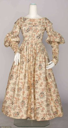 "GIRL'S DAY DRESS & PELERINE, 1837-1840  Cream cotton w/ stylized floral print in turquoise, brick red & yellow w/ black outlines, sleeve tops ruched, piped bodice, double layer pelerine, B 31"", Hi W 25"", L 45"","