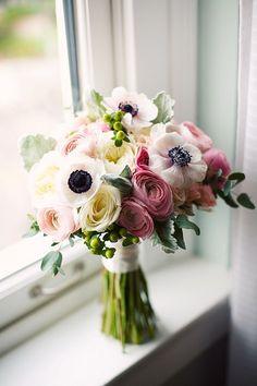Ranunculus, garden roses, anemones, hypericum berries and dusty miller.