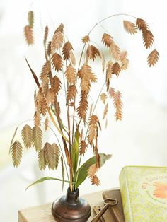 An old doorknob finds new purpose as a fall vase. Sea oats (Chasmanthium) are arranged to fit inside a handsome doorknob. Fill the doorknob with sand to add weight and stability to the arrangement.