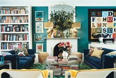 teal walls, colorful furniture, bookshelves, this is a very lived-in realistic look.