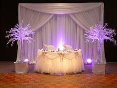 Sweetheart Table - All White with Lavender spot lights - www.sbdevents.com - Email: info@sbdevents.com. Location: Carson Community Center - Hall B - table skirt is patented by SBD EVENTS