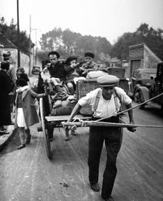 A man pulling a cart loaded with his children and valuables as he escapes from imminent Nazi occupation during World War II. Photograph by Carl Mydans. Paris, 1940.