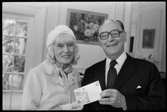 Aviator Jean Batten presenting a first-day stamp cover from Britain to the Governor General Sir Keith Holyoake. The 1976 cover, issued by the RAF Museum at Hendon, England, marked the 40th anniversary of Batten's famous 1936 journey, the first ever direct flight from England to New Zealand. Photograph taken circa 5 December 1979 by and unidentified Evening Post staff photographer.
