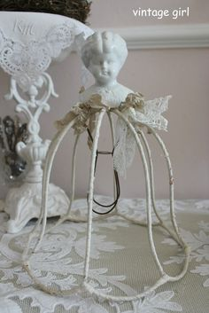 Beautiful creation with vintage doll head and wire base.