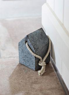 A house-shaped door stop in heavy granite