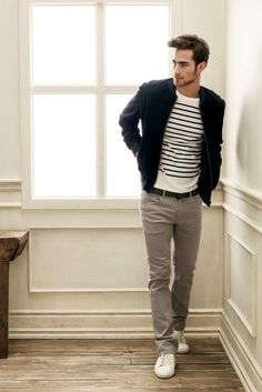 Striped sweater, zip-up jacket, grey pants with leather belt and white canvas tennis shoes.