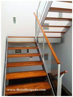 Escalera metálica con peldaños de madera y baranda de cristal. Fabricación Metal Delgado