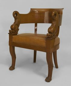 French Charles X maple round back arm chair with carved dolphin arms and a tan leather seat with gold tooled trim