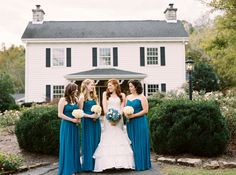 Bridal party in front of Dara's Garden in Knoxville, TN. Dresses from White Lace and Promises. Bridesmaid dresses by Dessy in ocean blue. Bride wearing ivory mermaid dress by Essense of Australia.