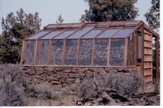 7x12 Tropic Lean-to greenhouse on lava rock base with lava rock back wall for solar mass - in Bend OR