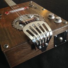 Distressed Resonator Guitar. Electric & acoustic. Made with mostly repurposed hardware: Paper towel holder, chrome spatula, old metal bowl, bicycle chainring. Headstock is oak with wood trim from discarded chair found in a dumpster. Tom Thompson-Primitive Acoustics