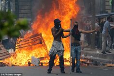 FRANCE IS IN TROUBLE  -   Protesters stand in front of a fire barricade near the aerial metro station of Barbes-Rochechouart in Paris amid violent clashes ||  http://static.mvlehti.net/uploads/2015/08/11958359_1133861679961595_558585151_n.mp4?_=1