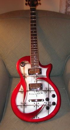 Custom guitar, LP style sort of. Looks a bit Danelectro or even Luna or Daisy. Great red and white contrast.