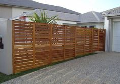 1800 high Balau timber fence with gate attached to side of house and rendered retaining wall
