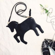 "Black My Little Pony Clutch This clutch is SO cute! Black faux leather in the shape of a unicorn. Shown with optional detachable shoulder strap that adjusts from 30-55"" long. Little loops of fabric create a mane and the tail is the pull for the gold zipper closure along its back. 8.5 x 4"" interior is just the right size for your phone, ID/cash and lip gloss - perfect for going out! Minor scuffing from storage but otherwise no issues!     Reasonable Offers Accepted No Trades 15% Bundle…"