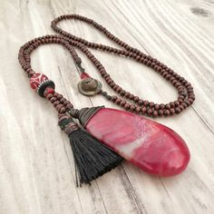 This is a long, bohemian, wooden bead and tassel necklace with a large red jade…